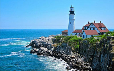 Lighthouse and Inn keepers house on a rocky point in Portland, Maine.