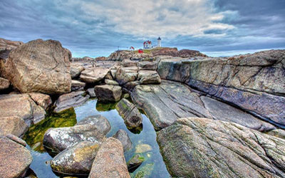View of the shoreline rocks and lighthouse in Portland, Maine.