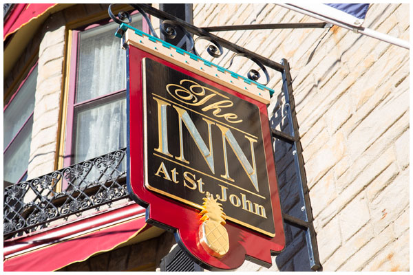 Sign hanging in front of the Inn at St. John hotel in Portland, Maine with company coat of arms.