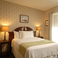 Queen bed with table lamps of a value accommodation at the Inn at St. John.