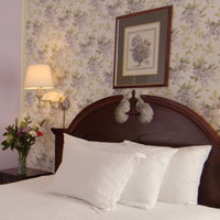 White pillows and head board in a traditional accommodation room at the Inn at St. John in Portland, Maine.